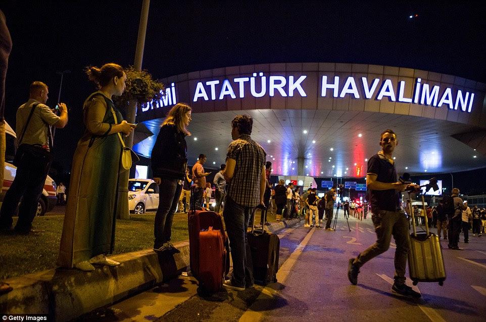 Os passageiros estão com sua bagagem fora do aeroporto como as luzes de veículos de serviço de emergência pode ser visto mais perto da cena