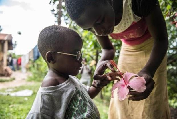 """A prima de Criscent lhe explica o que é uma flor em frente à casa da família em Bundibugyo. """"Adquirir visão é um processo"""", disse Magyezi. """"Com os óculos, Criscent vai aprender a usar seus olhos e o que vê através deles. Assim poderá interpretar o mundo"""". (Foto: Tommy Trenchard / Sightsavers)"""