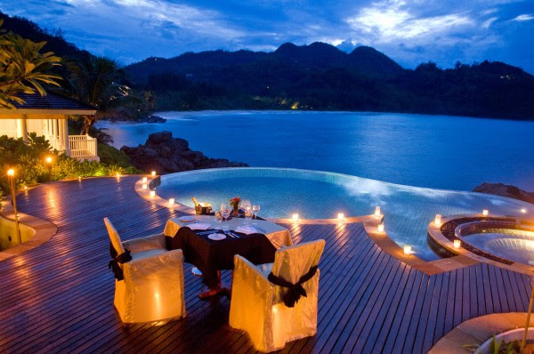 dining by round infinity pool overlooking ocean cliffs