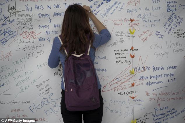A visitor writes on a banner carrying messages for the passengers of missing Malaysia Airlines flight MH370 at Kuala Lumpur International Airport