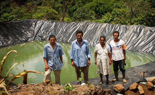 (L to R) Pedro Ramos, Víctor de León, Ofelia Chávez and Daniel Santos, in front of one of the two rainwater reservoirs built in their village, La Colmena, in the Salvadoran municipality of Candelaria de la Frontera. The pond is part of the benefits of a climate change adaptation project implemented by FAO. Credit: Edgardo Ayala/IPS
