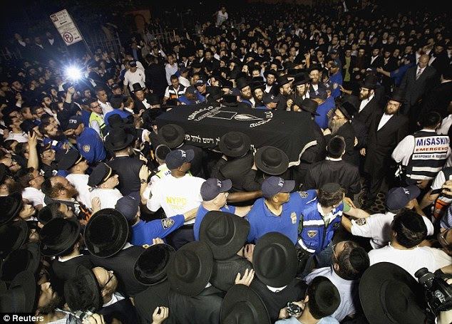 Devastated community: Leiby Kletzky's body is carried high above thousands of black-clad mourners who gathered in Brooklyn last night for his funeral. His dismembered body was found just hours before