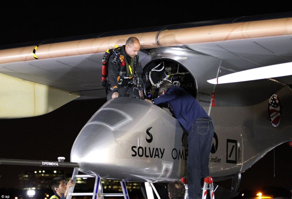 The Solar Impulse pilot Bertrand Piccard, left, enters the cockpit before taking off