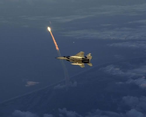 An F-15 fighter jet patrols the skies above Kennedy Space Center just as a space shuttle is lifting off.