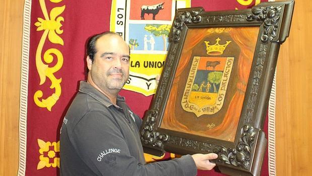 Mayo muestra los dos escudos que lucen hoy en el Ayuntamiento