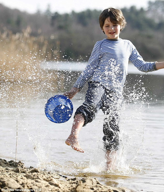 Spring on its way: Oliver Lawrence, eight, splashes in the water at Frensham Pond today. Forecasters are predicting temperatures of 18C next week