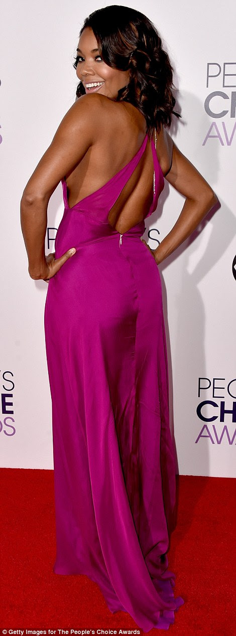 Pretty in bright pink: Gabrielle Union showed off her curves in a very alluring hot pink satin dress with a plunging neckline and a flattering cris-cross design in the back
