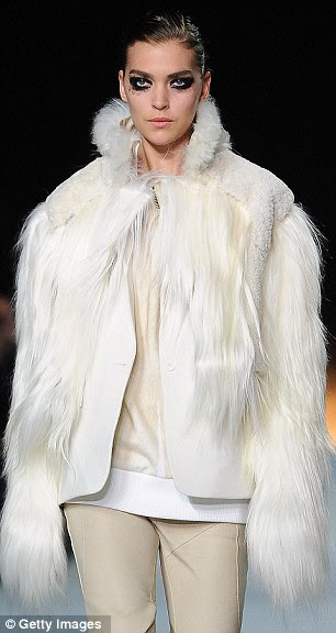 Surely she doesn't need the money? Arizona Muse was draped in white fur at the Paris show