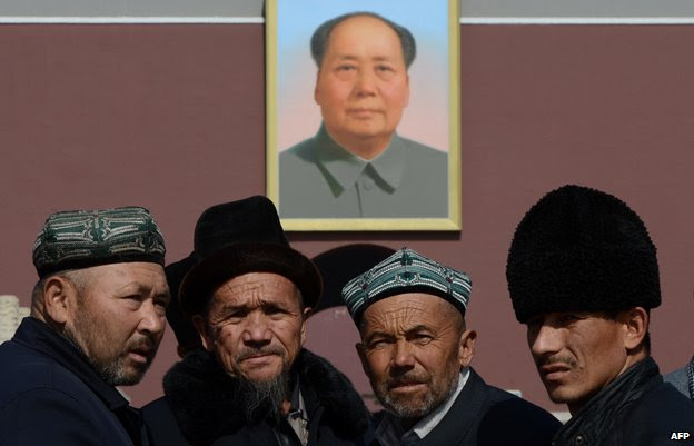 Uighurs pose for photos in front of a portrait of Mao Zedong in Beijing on March 3, 2013