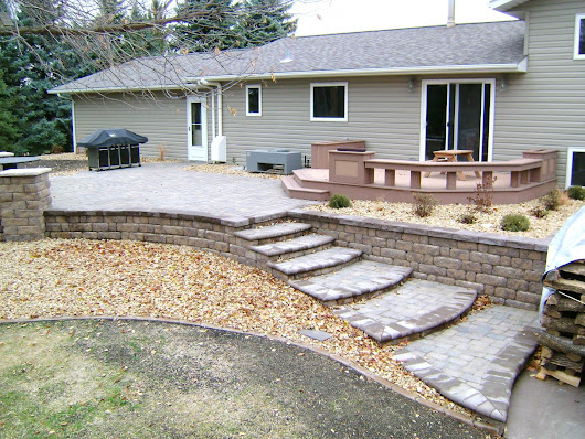 Raised Paver Patio with Retaining Walls, Stairs, Deck, and Seating Wall | Oasis Landscapes | West Fargo ND