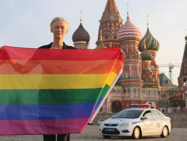 Tilda Swinton with a rainbow flag in front of the Kremlin