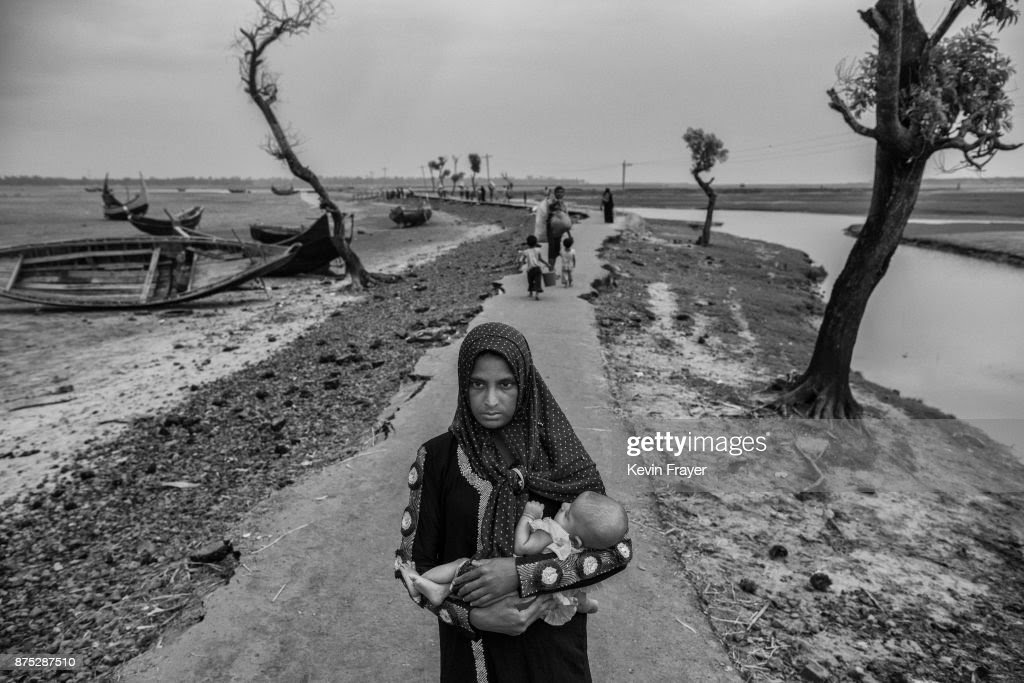 COX'S BAZAR, BANGLADESH - OCTOBER 29: A newly arrived Rohingya refugee woman carries her child as she walks on a broken road after arriving at Shah Porir Dwip on October 29, 2017 near Cox's Bazar, Bangladesh. More than 600,000 Rohingya refugees have flooded into Bangladesh to flee an offensive by Myanmar's military that the United Nations has called 'a textbook example of ethnic cleansing'. The refugee population continues to swell further, with thousands more Rohingya Muslims making the perilous journey on foot toward the border, or paying smugglers to take them across by water in wooden boats. Hundreds are known to have died trying to escape, and survivors arrive with horrifying accounts of villages burned, women raped, and scores killed in the 'clearance operations' by Myanmar's army and Buddhist mobs that were sparked by militant attacks on security posts in Rakhine state on August 25, 2017. What the Rohingya refugees flee to is a different kind of suffering in sprawling makeshift camps rife with fears of malnutrition, cholera, and other diseases. Aid organizations are struggling to keep pace with the scale of need and the staggering number of them - an estimated 60 percent - who are children arriving alone. Bangladesh, whose acceptance of the refugees has been praised by humanitarian officials for saving lives, has urged the creation of an internationally-recognized 'safe zone' where refugees can return, though Rohingya Muslims have long been persecuted in predominantly Buddhist Myanmar. World leaders are still debating how to confront the country and its de facto leader, Aung San Suu Kyi, a Nobel Peace Prize laureate who championed democracy, but now appears unable or unwilling to stop the army's brutal crackdown.