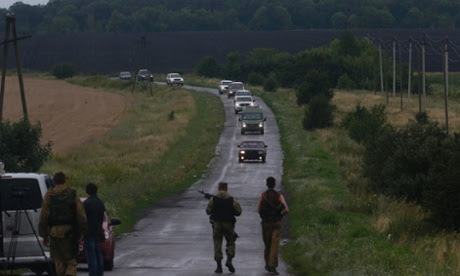 Pro-Russian separatists watch as OSCE monitors arrive at the crash site of Malaysia Airlines flight MH17, near the settlement of Grabovo ukraine