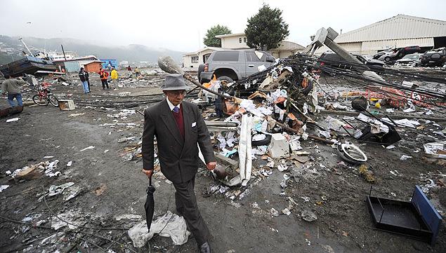 Morador de Talcahuano caminha em meio a destruição após tsunami; governo é obrigado a indenizar família por aviso falso
