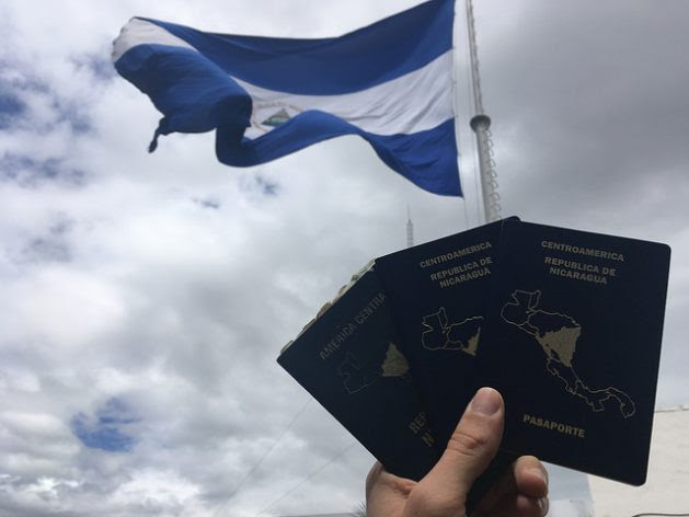 """With a Nicaraguan flag in the background, passports from Nicaragua, with the silhouette of Central America on its cover, are held up. The country's southern border with Costa Rica is closed by a """"containment wall"""" policy that keeps out migrants travelling from South America towards the United States. Credit: José Adán Silva / IPS"""