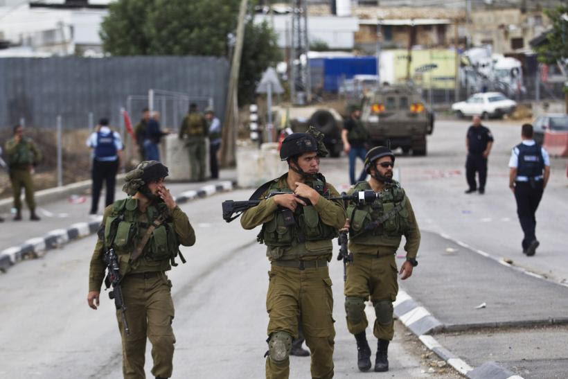 Israeli soldiers walk in formation while on patrol