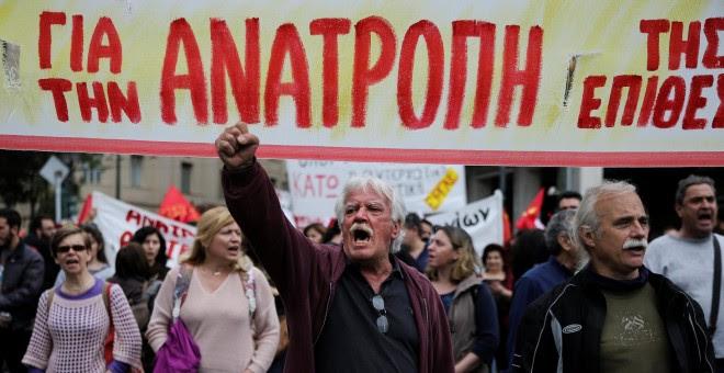 Manifestantes marchan ´con una pancarta en la que se lee 'Subversión' en la protesta convocada la huelga general contra los últimos recortes pactados con la UE. REUTERS/Alkis Konstantinidis