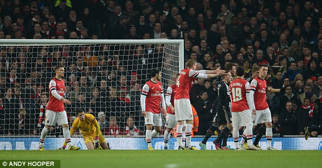 Let the inquest begin: Per Mertesacker (centre) shows his unhappiness at Muller's goal