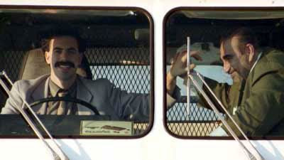 Borat and his producer/wrestling-partner Azamat high-five in their $600 ice cream truck.