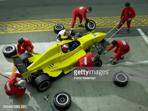 Pit Crew Changing Tires On Formula 1 Race Car Elevated
