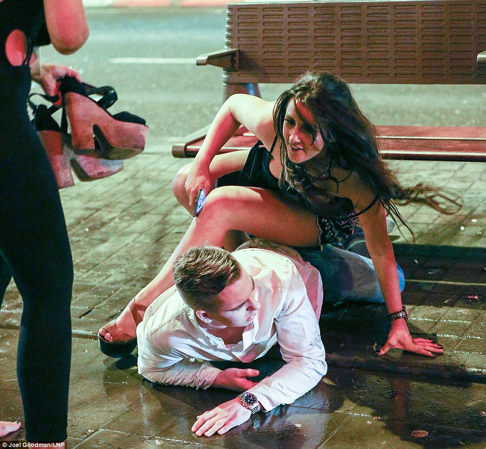 Fall: The bemused looking young man then fell to the floor with this young woman on top of him outside the Manchester Printworks club