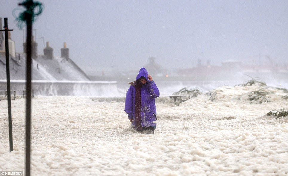 A woman makes her way through South Square in Fittie on the coast at Aberdeen, that has been covered in a thick sea foam after flooding from the North sea