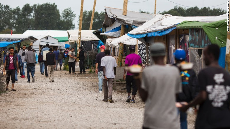Migrants walk past make-shift shops and shelters by the Jungle Books Cafe at the Jungle migrant camp in Calais, France.