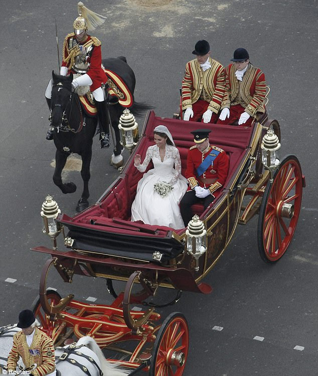 Catherine, Duchess of Cambridge, and Prince William wave to the vast crowds as they travel to Buckingham Palace in a 1902 State Landau