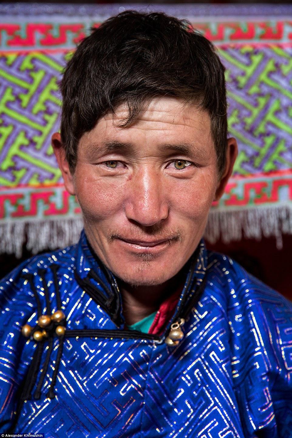 Um homem nômade mongol de Tavan Bogd veste um casaco azul muito bem trabalhada com sinos enquanto o Sr. Khimushin o viu durante a viagem na área remota