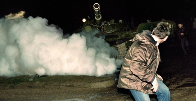 Un manifestante lituano corre frente a un tanque del ejército soviético durante el asalto a la estación de radio y televisión lituana el 13 de enero de 1991. AFP
