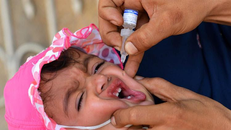 A health worker administers polio vaccination drops to a child in Peshawar, on May 20, 2014