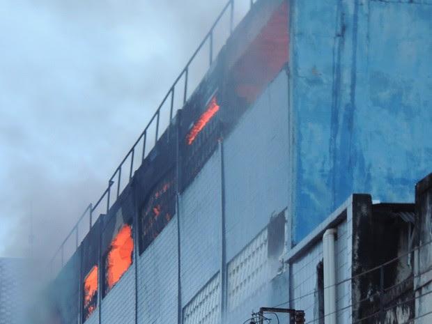 Às 17h30, com menos fumaça, era possível ver as chamas que consumiam o interior do prédio (Foto: Katherine Coutinho / G1)