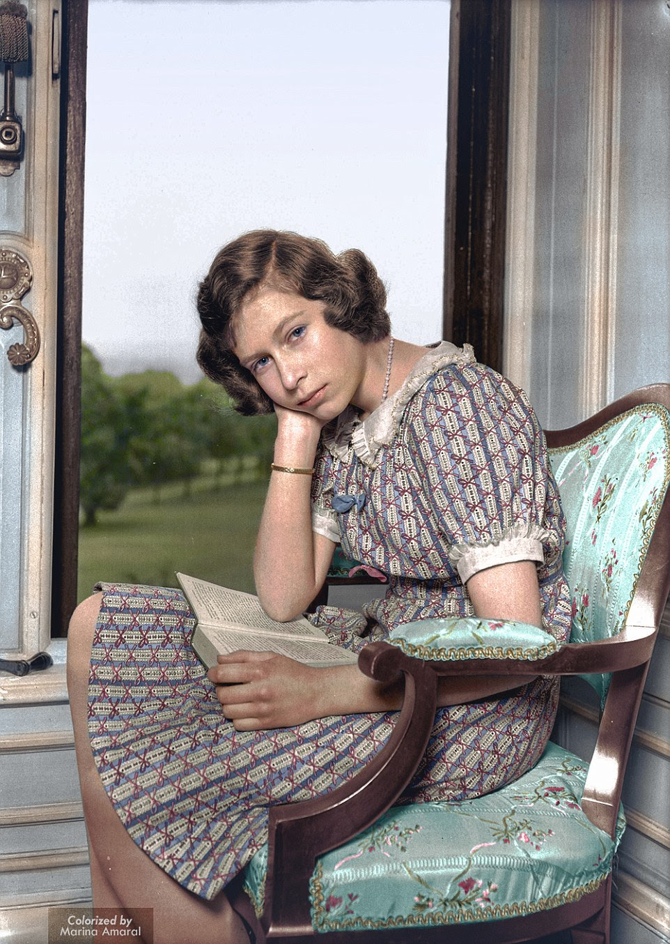 Regal: A fourteen-year-old Queen Elizabeth II, when she was a mere princess, is pictured here sat by the window with her nose in a book