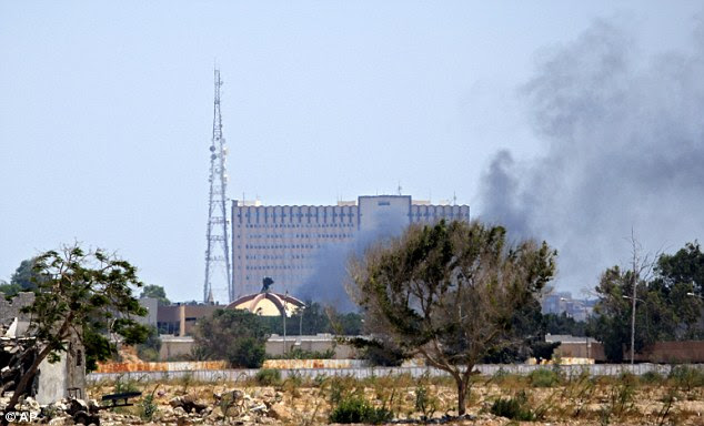 Under siege: Smoke rises over buildings in Gaddafi's main compound in the Bab al-Aziziya district of Tripoli today after an attack by rebels