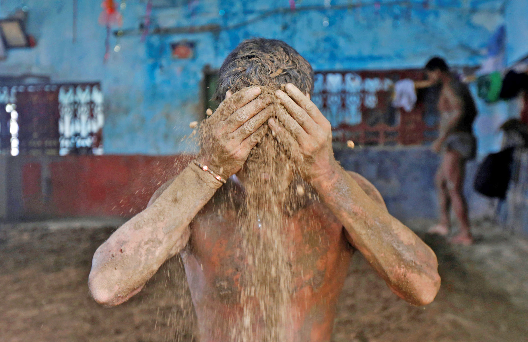 A wrestler applies mud to prevent slipping due to sweat, at a traditional training centre on the banks of the river Ganges ahead of the Bengal mud wrestling championships, in Kolkata, India today