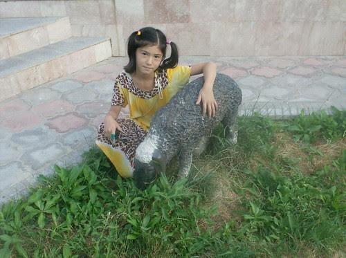 Young Tajik girl with sheep statue at Boq-i botaniki in Dushanbe, Tajikistan