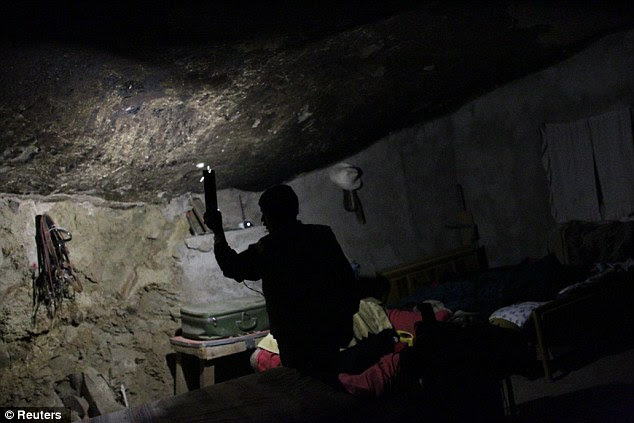 Little electricity: The home has unreliable electricity so Adan Hernandez, Benito's son, holds a flashlight inside the family's bedroom