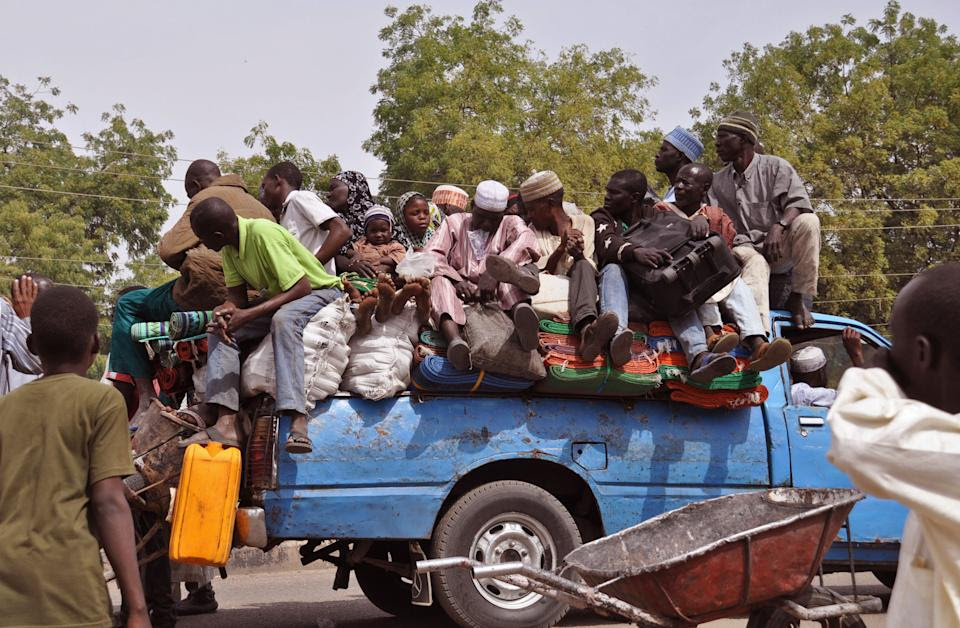 In this photo taken Tuesday, Jan. 27, 2015, villagers sit on the back of a small truck as they and others flee the recent violence near the city of...
