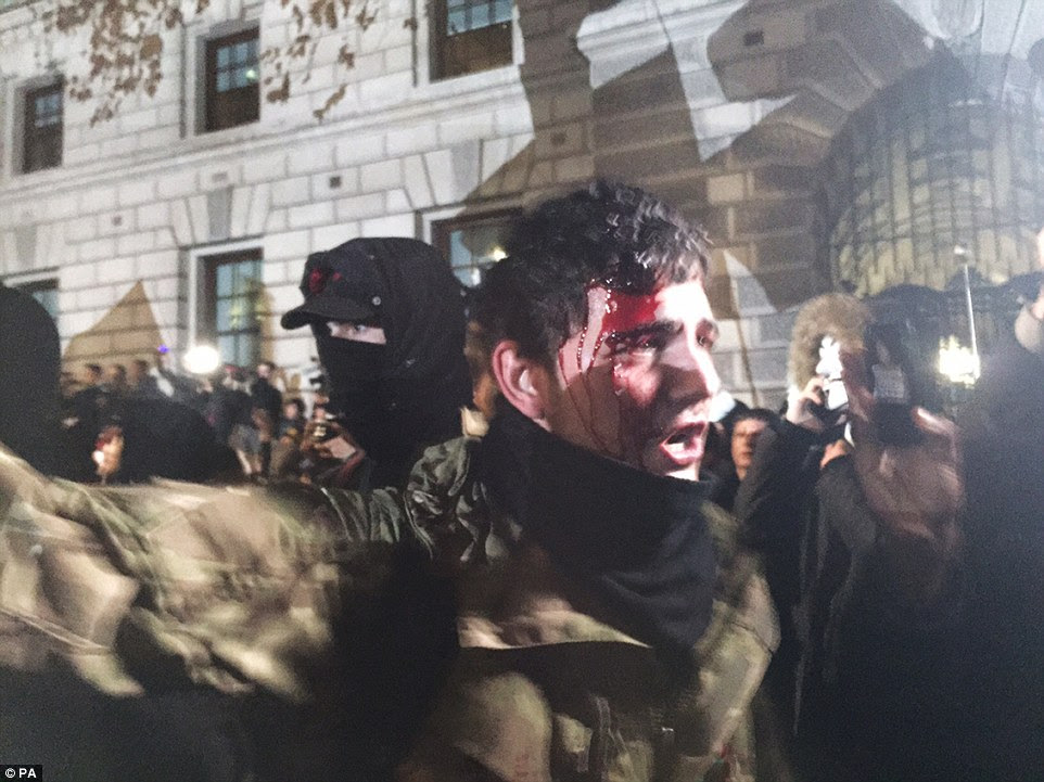 A protester comes out with a bloodied head as crowds surge forward on Great George Street in central London