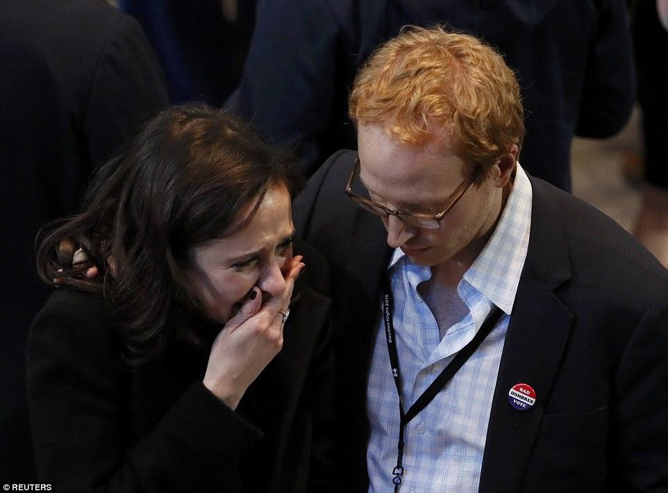 Uma mulher na reunião de Nova York Hillary Clinton chora como um homem conforta
