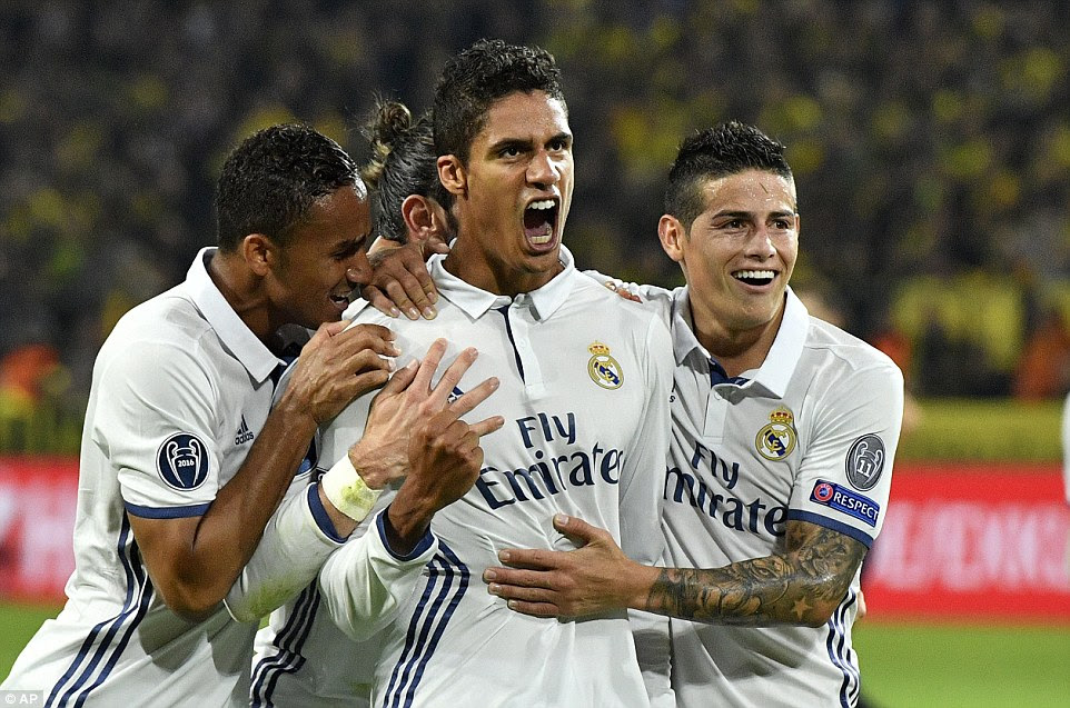 Varane is mobbed by team-mates after his late effort secures an impressive away win for the Spanish giants