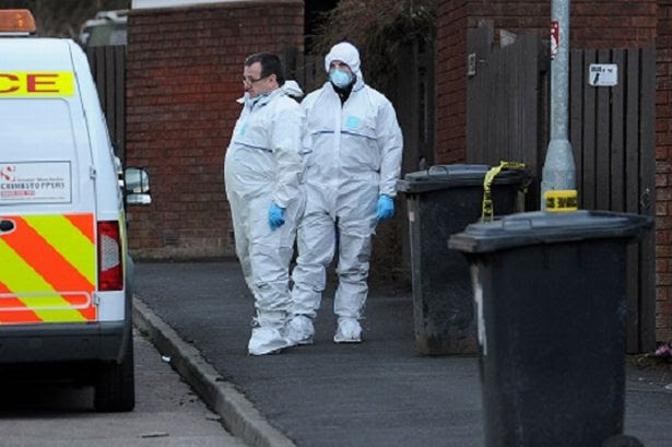 Police and forensics stands outside the front door of a house in Chaucer Grove, Atherton