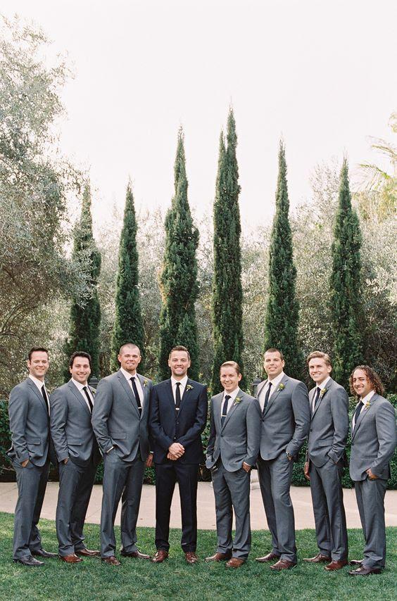 Trauzeugen gekleidet in graue Anzüge mit schwarzen Krawatten und der Bräutigam im schwarzen zu stehen