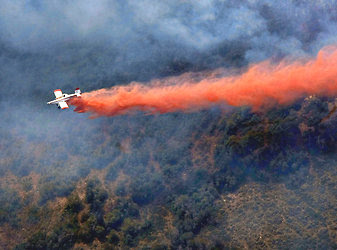 An air tanker dropping retardant on a wildfire near Mount Pleasant, Utah, on Monday. Firefighters have nearly contained the Dump Fire in that state.