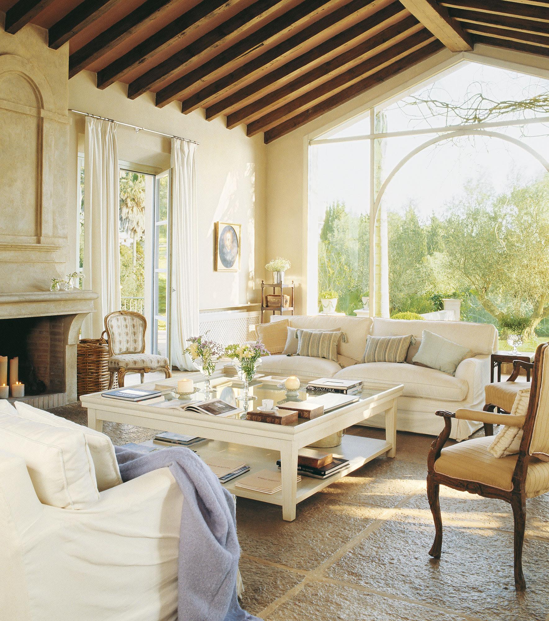 Salón con suelo de terrazo, techo abuhardillado y pared de cristal hacia el jardín