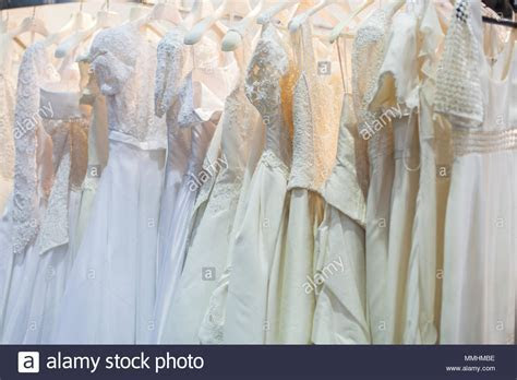 Beautiful wedding dresses hang on hangers on the rack
