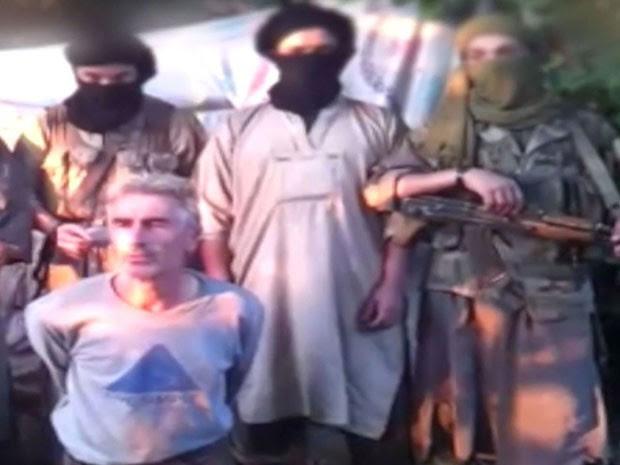 Vídeo mostra refém dominado por militantes armados e encapuzados (Foto: Ho/Jund Al Khaliva/YouTube/AFP)