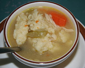 A bowl of chicken and dumplings with vegetable...