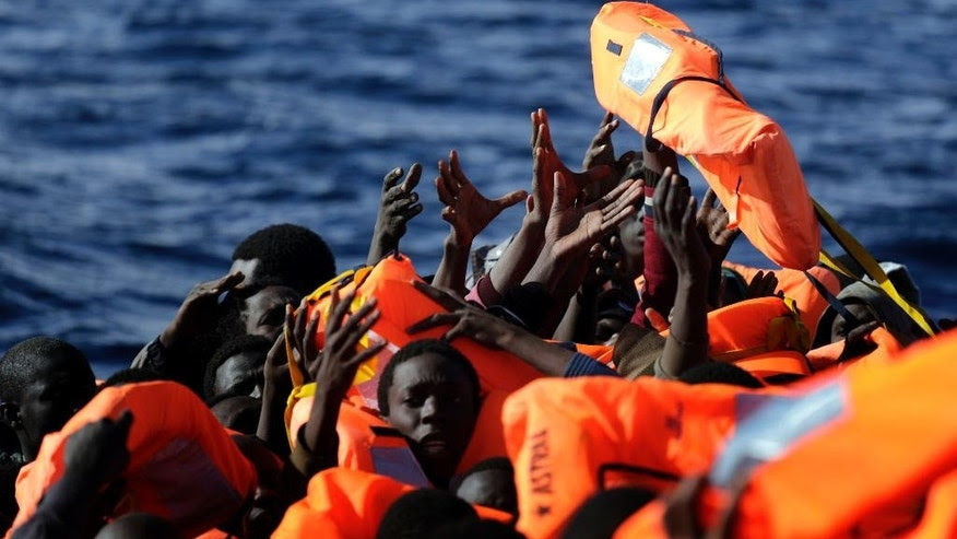 FILE - In this Jan. 27, 2017 file photo, sub-Saharan migrants raise their hands to grab a life jacket as they are rescued by members of the Proactive Open Arms NGO, in the Mediterranean Sea north of Zumarah, Libya. European Union President Donald Tusk said on Thursday, Feb. 2, 2017, that a summit on migration on Friday, Feb. 3, 2017, is poised to take a big step in closing off the illegal migration route through the central Mediterranean where thousands have died over the past several years trying to reach the EU from Libya. (AP Photo/Emilio Morenatti, File)