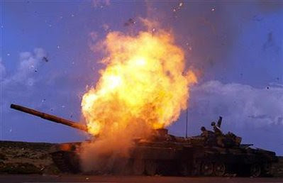 A tank belonging to forces loyal to Libyan leader Muammar Gaddafi explodes after an air strike by coalition forces, along a road between Benghazi and Ajdabiyah March 20, 2011. REUTERS/Goran Tomasevic by Pan-African News Wire File Photos